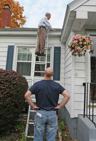 LORI VAN BUREN/TIMES UNION -- Wynn Englisbe, on ladder, talks to home purchaser Vinny Ciccarelli, as he inspect the roof of a home in Rotterdam, NY on October 13, 2008. For cover story of Sunday's real estate section. ORG XMIT: MER2014090308350327 Photo: LORI VAN BUREN / 00000732A