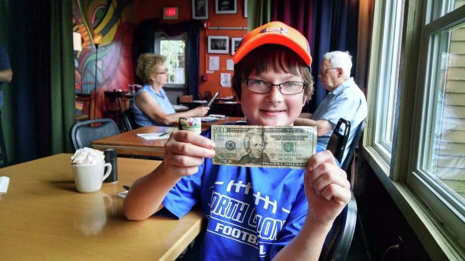 Bobby Dennis, 10, of Latham, Monday holds up his newly found $20 at Professor Java's Coffee Sanctuary in Colonie. This is the second time Bobby has found a $20 by following clues from the Facebook page Find A Twenty. (Keshia Clukey/ Times Union)