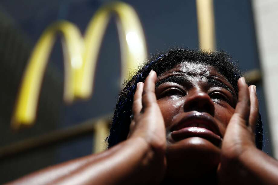 Archenemies? Angela Owens, who works in the health care industry, wipes tears from her eyes as she speaks to members of the media at a protest to push fast-food chains to pay their employees at least $15 an hour outside a McDonald's restaurant in Philadelphia.  Photo: Matt Rourke, Associated Press