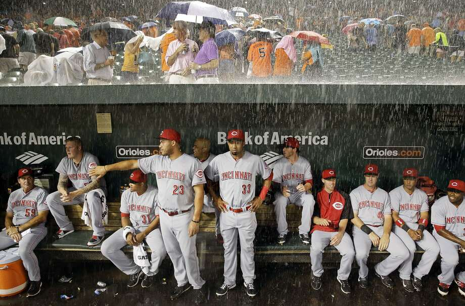 Better Red than wet:Members of the Cincinnati Reds watch from the dugout as heavy rain falls during a rain delay in their game against the Orioles in Baltimore. Photo: Patrick Semansky, Associated Press