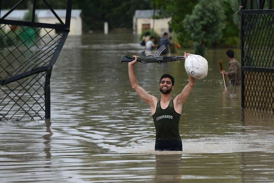 Keep your powder dry:An Indian policeman holds his weapon while negotiating flood waters on the outskirts of Srinagar in the Kashmir Valley. Flooding has left at least 16 people dead. Photo: Tauseef Mustafa, AFP/Getty Images
