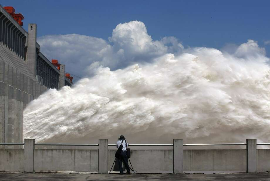 Releasing the pressure:A man takes pictures of floodwater released from the Three Gorges Dam, a gigantic hydropower project on the Yangtze River in central China's Hubei province, after heavy downpours in the upper reaches of the dam caused the highest flood peak of the year. Eleven people died and 27 others are missing. Photo: Stringer, AFP/Getty Images