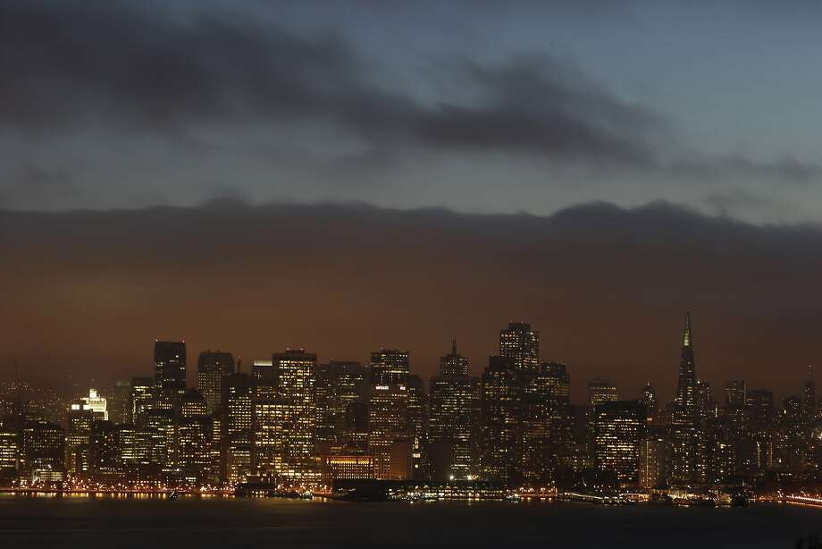 Rolling back in: Fog covers the San Francisco skyline at dusk. Photo: Marcio Jose Sanchez, Associated Press