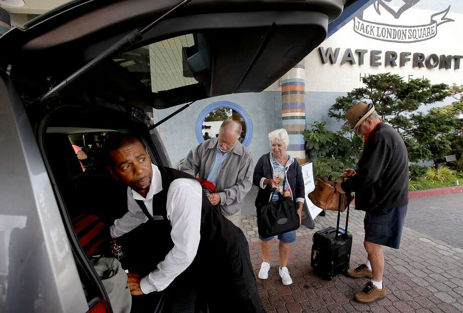 Waterfront Hotel valet Andre Logan loads luggage for guests John (left center), Darlene and Jim Hedrick. Photo: Michael Macor, The Chronicle