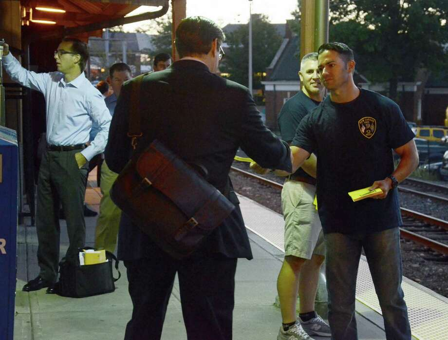 Police officer George Caponera hands out a flier to a commuter at the New Canaan train station early Thursday morning, Sept. 4, 2014. Caponera is a member of New Canaan Police Union Local 1575, which was at the station seeking support from residents as a contract dispute with the Town of New Canaan, Conn., continues into a second year. Photo: Nelson Oliveira / New Canaan News