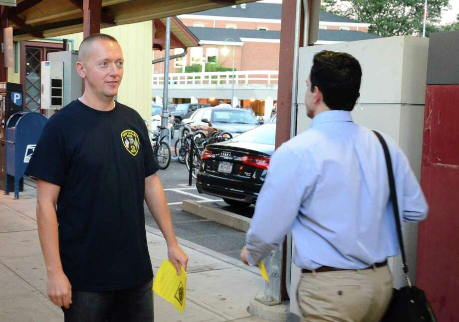 Sgt. John Milligan, president of New Canaan Police Union Local 1575, hands out a fliers at the New Canaan train station early Thursday morning, Sept. 4, 2014. Photo: Nelson Oliveira / New Canaan News