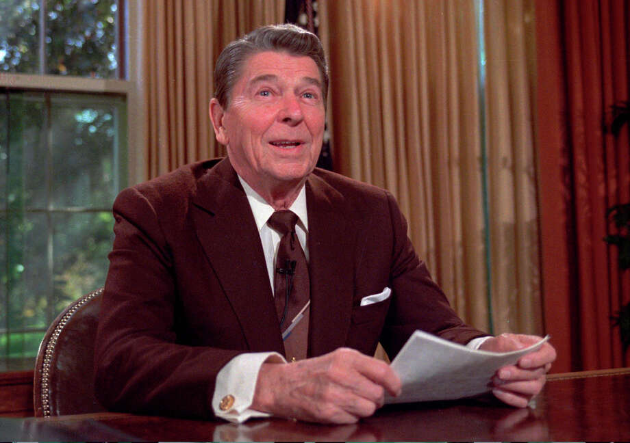 FILE - In this May 24, 1985 file photo, President Ronald Reagan works at his desk in the Oval Office of the White House as he prepares a speech on tax revision in Washington.  President Barack Obama's summer fashion choice, not unprecedented among presidents - himself included - was the talk of social media, Thursday, Aug. 28, 2014. Other presidents who have taken on tan include Bill Clinton, Ronald Reagan, George H. W. Bush, George W. Bush and Dwight Eisenhower. George W. Bush and Reagan also wore brown suits.  (AP Photo/Scott Stewart, file) ORG XMIT: CAET575 Photo: Scott Stewart / AP