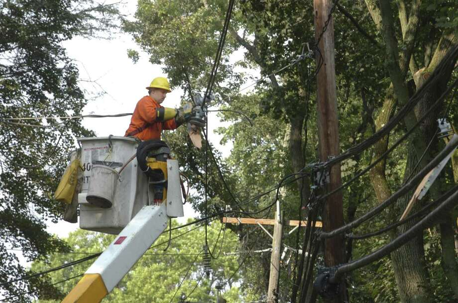 Mark Guell, from CL&P, works with the broken electric lines after a tree fell across North Street in Greenwich, Conn. Photo: Helen Neafsey, File Photo / Greenwich Time