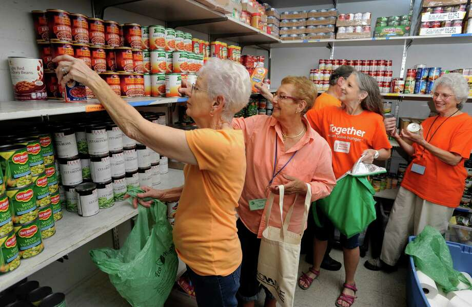 "Volunteers at New Milford Food Bank, in New Milford, Conn., dressed in orange t-shirts, work in the pantry Thursday, Sept. 4, 2014. They are from left, Jane Gsell, June Gawel, Donnie Franco, part-hidden, Terri Gatten and Ann Vallombroso. This month is ""Hunger Action Month"" and people are asked to wear orange to draw attention to hunger in this country. Photo: Carol Kaliff / The News-Times"
