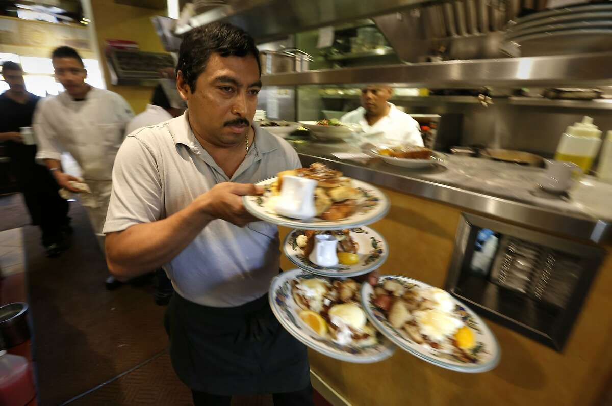 Waiter Jose Beltran picks up an order from the kitchen at Zazie restaurant, in San Francisco, Calif., on Wednesday Aug. 27, 2014. Jen Piallat owner of Zazie offers her employees fixed schedules, full benefits and matching 401k plans and she says her business is more successful for it.