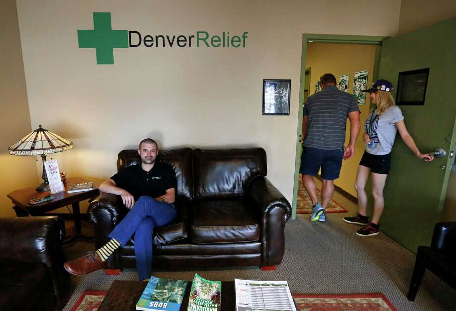 In this Aug. 25, 2014 photo, Kayvan Khalatbari, left, sits on the couch in the lobby of his medical and recreational marijuana store Denver Relief, as his employee Allison Woods escorts a customer into the shop, in Denver. Khalatbari also runs Denver Relief Consulting, which assists current and would-be marijuana-related businesses around the country, as well as owning a chain of pizza restaurants in Denver. (AP Photo/Brennan Linsley) ORG XMIT: COBL301 Photo: Brennan Linsley / AP