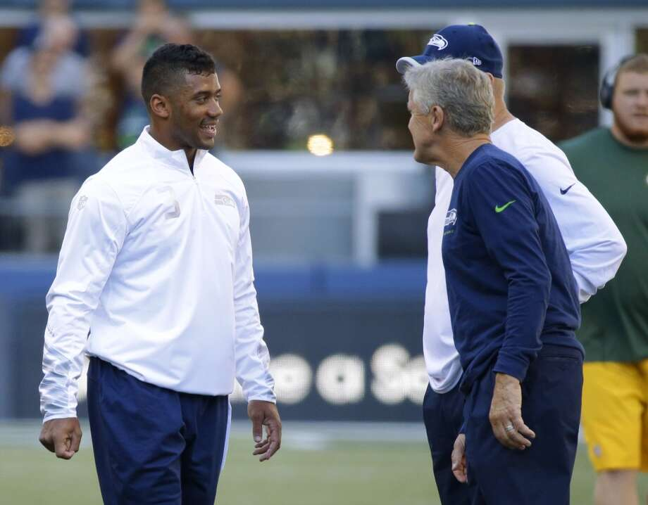 Seattle Seahawks quarterback Russell Wilson, left, talks with head coach Pete Carroll, center, and offensive coordinator Darrell Bevell, right, during warm-ups before an NFL football game against the Green Bay Packers, Thursday, Sept. 4, 2014, in Seattle. (AP Photo/Elaine Thompson) Photo: Elaine Thompson, AP