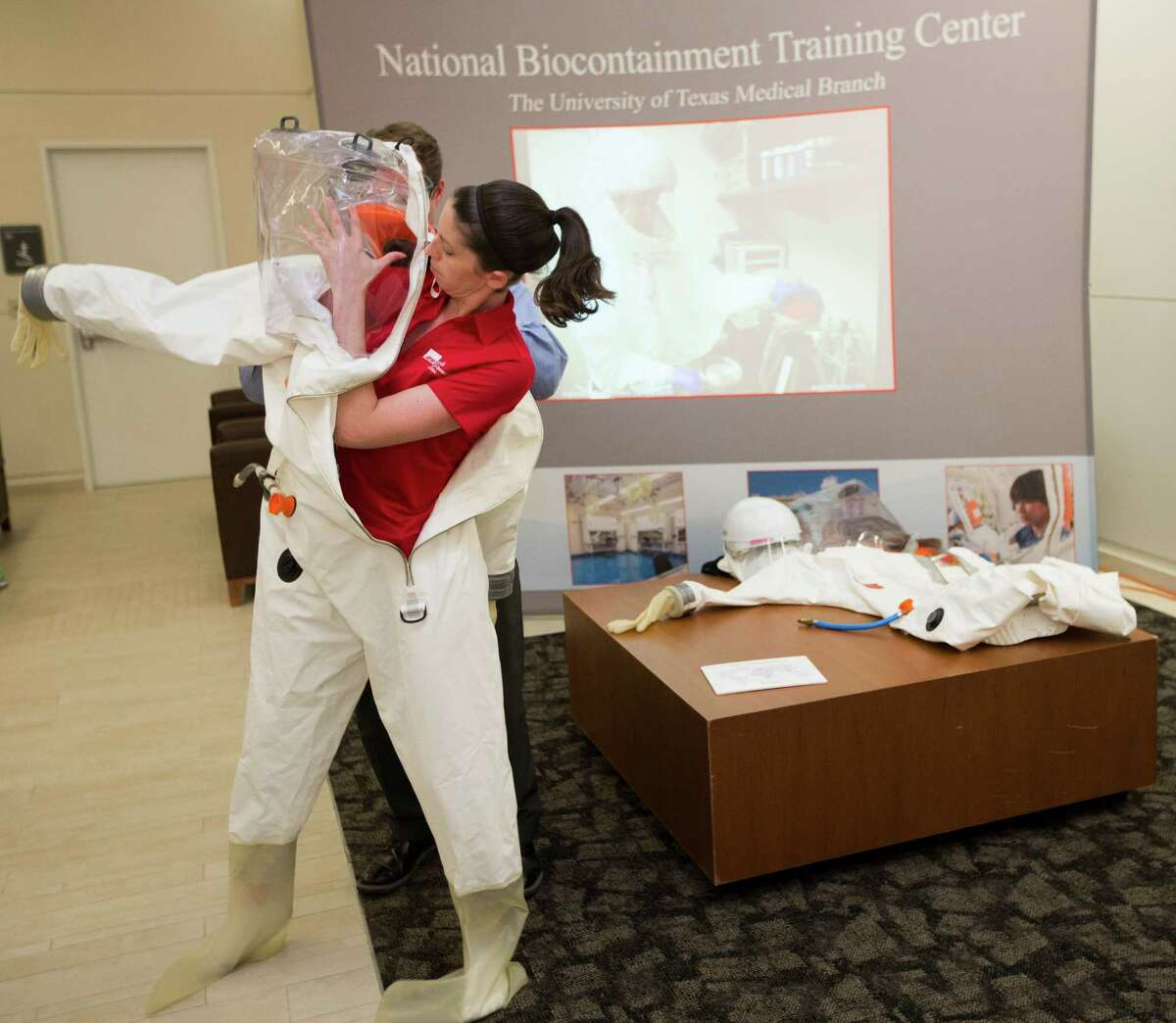 Corrie Ntiforo, environmental health and safety consultant, dons a positive pressure suit Thursday for a demonstration at the Galveston National Laboratory at UTMB.