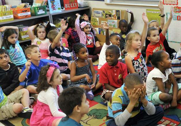 Students listen and some raise their hands to answer a plot question as first year teacher Christina Hannah reads the book, First Day Jitters, to her first grade class on their first day of school at Eagle Point Elementary on Thursday Sept. 4, 2014 in Albany, N.Y.  (Michael P. Farrell/Times Union) Photo: Michael P. Farrell / 00028468A