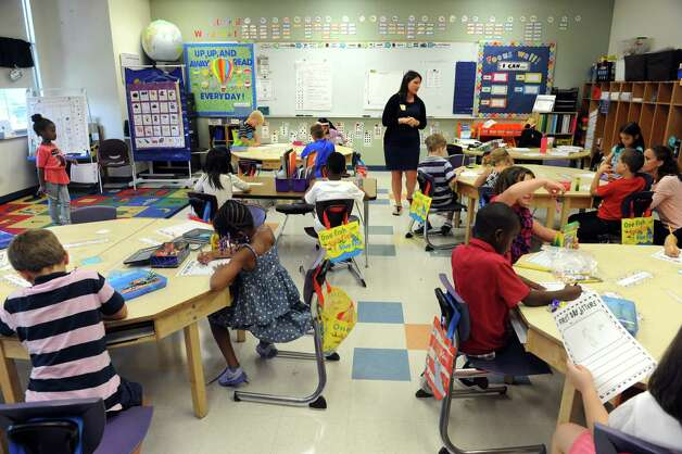 First year teacher Christina Hannah, left, goes over a comprehension assignment after she read the book, First Day Jitters,to her first grade class on their first day of school at Eagle Point Elementary on Thursday Sept. 4, 2014 in Albany, N.Y.  (Michael P. Farrell/Times Union) Photo: Michael P. Farrell / 00028468A
