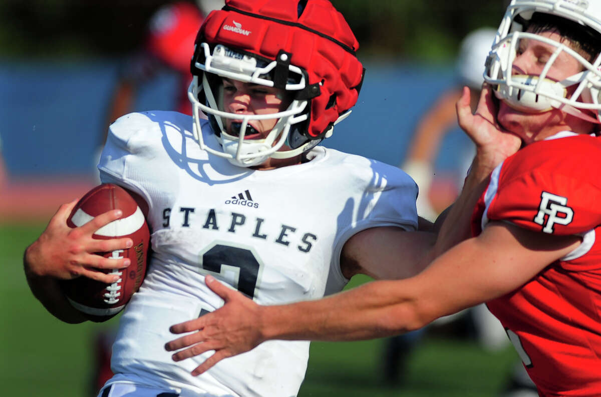 Staples QB Teddy Coogan pushes away a Fairfield Prep player, during football scrimage action in Westport, Conn. on Thursday September 4, 2014.