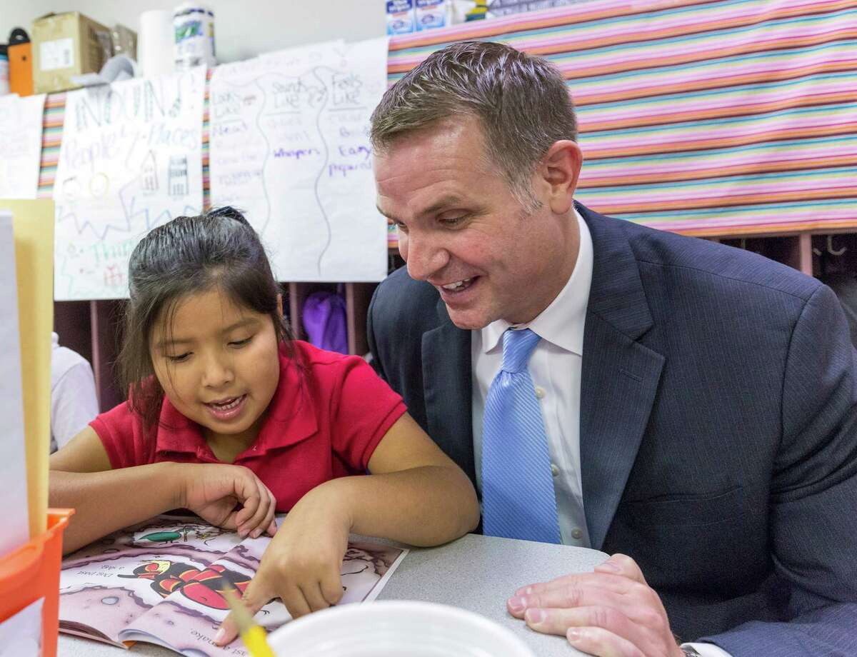 """Elementary curriculum officer Lance Menster and 6-year-old Genesis Sanchez pair up Thursday to debut HISD's """"Read Houston Read"""" literacy program at Garcia Elementary, 9550 Aldine Westfield."""