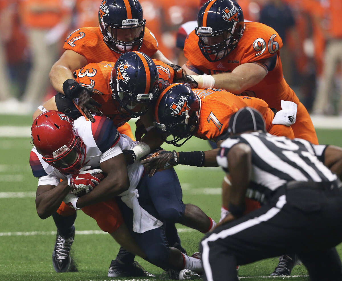 Roadrunner defenders swarm over to stop Nick Wilson in the first half as UTSA hosts Arizona in its home opener at the Alamodome on September 4, 2014.