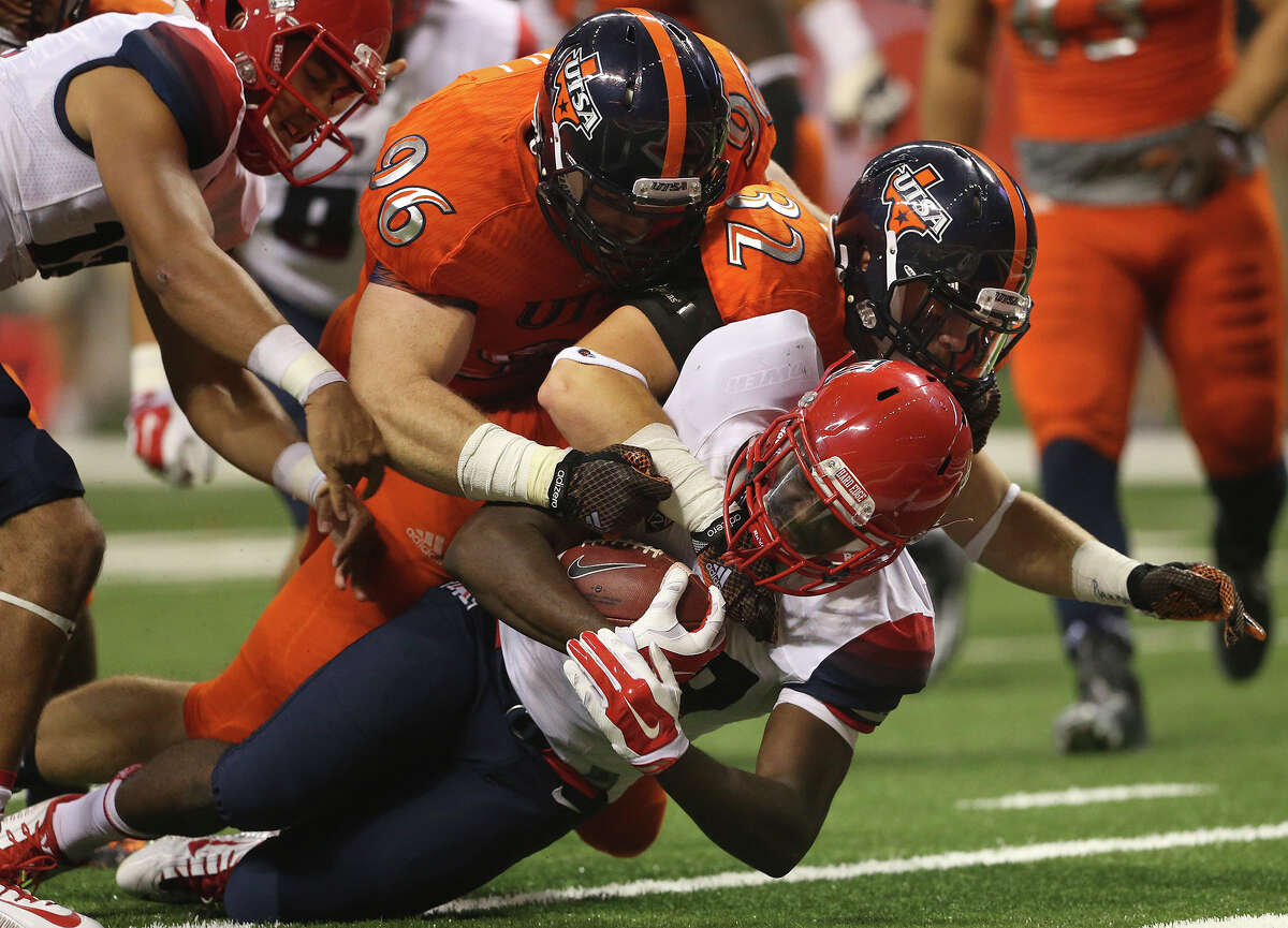 Roadrunner defenders Jason Neill (96) and Drew Douglas push running back NIck Wilson back for a one yard loss setting up a touchback as UTSA hosts Arizona in its home opener at the Alamodome on September 4, 2014.