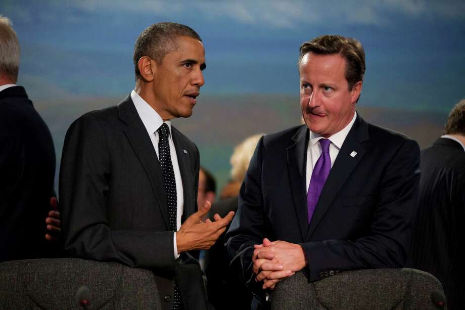 U.S. President Barack Obama and British Prime Minister David Cameron, right, speak before taking their seats at the start of a NATO-Afghanistan round table meeting during a NATO summit at the Celtic Manor Resort in Newport, Wales on Thursday, Sept. 4, 2014. In a two-day summit leaders will discuss, among other issues, the situation in Ukraine and Afghanistan.  (AP Photo/Matt Dunham) ORG XMIT: LMD113 Photo: Matt Dunham / AP