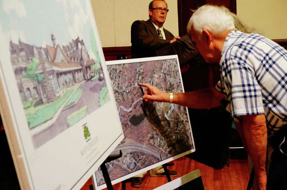 Residents look over the plans for a proposed assisted living facility on Mill Hill Terrace at a meeting for neighbors Thursday. Photo: Genevieve Reilly / Fairfield Citizen