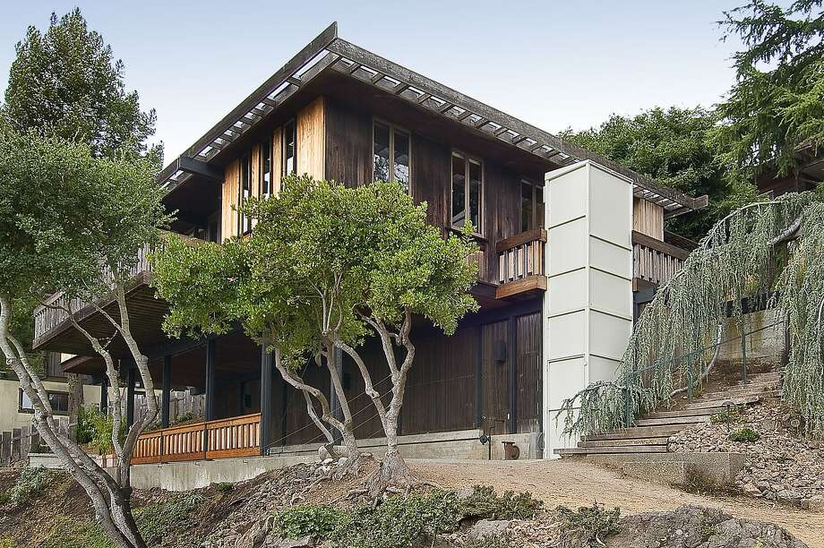 The exterior of the two-story mid-century features earth tones and multiple outdoor spaces.  Photo: Open Homes Photography