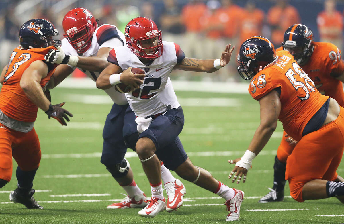 Wildcat quarterback Anu Solomon runs but can't escape the pursuing Ferrrington Macon as UTSA hosts Arizona in its home opener at the Alamodome on September 4, 2014.