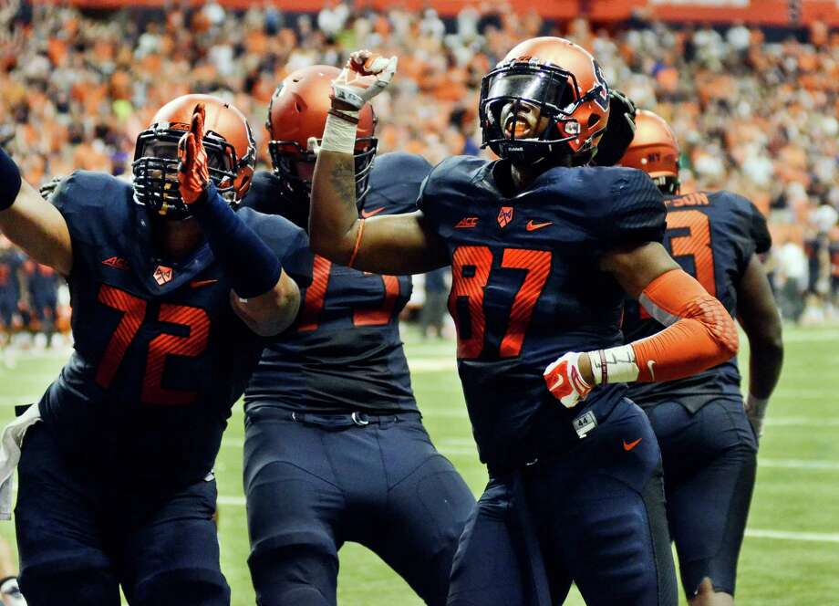 Syracuse's Kendall Moore, right, celebrates with teammates after his touchdown reception in the second overtime game Syracuse a 27-26 win over Villanova in an NCAA college football game Friday, Aug. 29, 2014, in Syracuse, N.Y. (AP Photo/Heather Ainsworth) ORG XMIT: NYHA207 Photo: Heather Ainsworth / FR120665 AP
