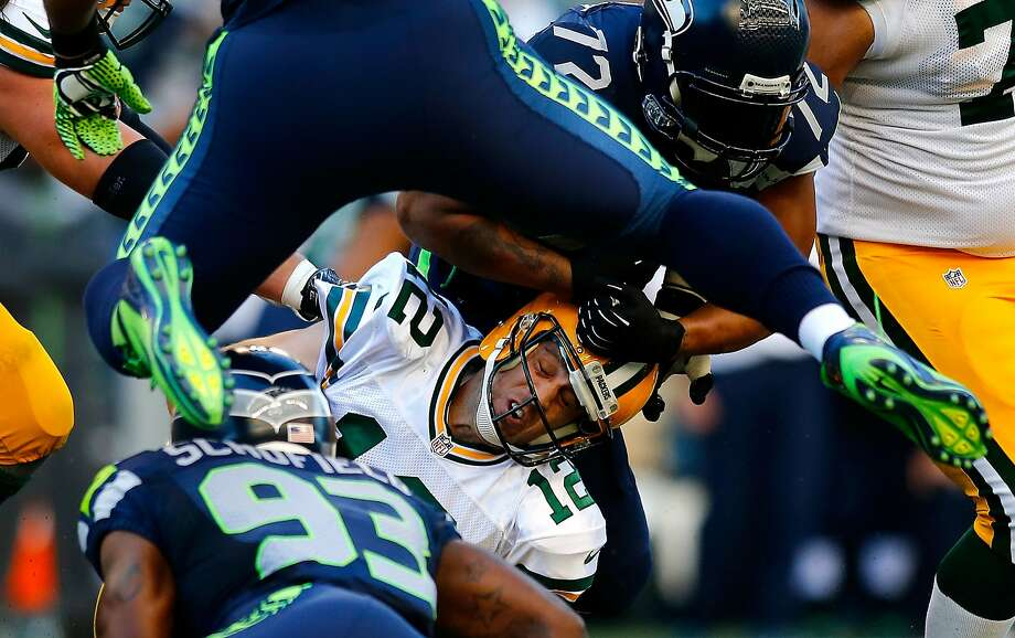 Packers quarterback Aaron Rodgers (12) was sacked three times by the Seahawks in the NFL opener, including once by O'Brien Schofield (93) and Michael Bennett (72). Photo: Jonathan Ferrey, Getty Images