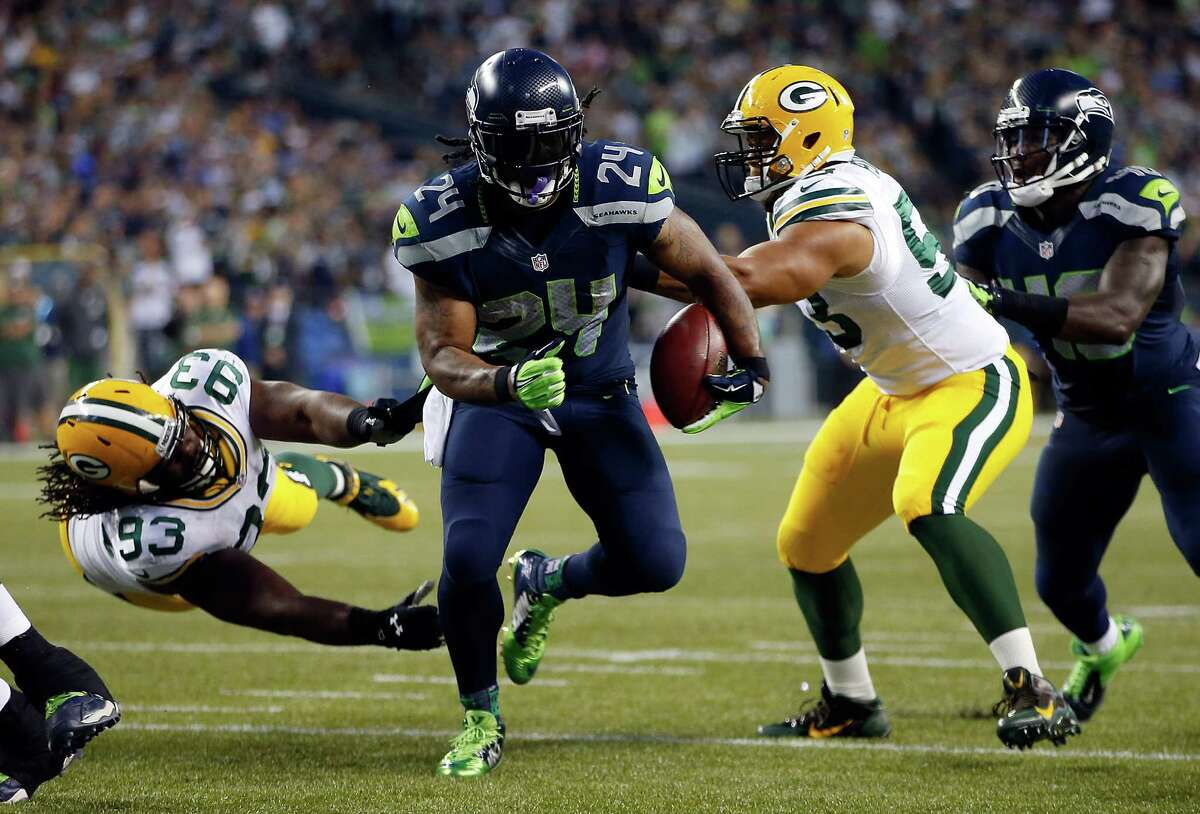 The Seahawks' Marshawn Lynch, who ran for 110 yards and two touchdowns, eludes two Packers in Seattle's 36-16 win over Green Bay on Sept. 4.