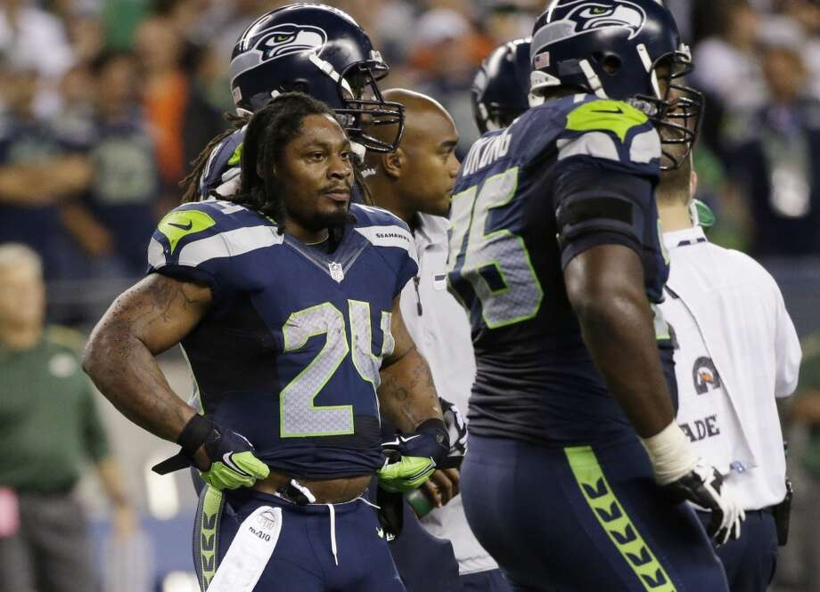 Seattle Seahawks running back Marshawn Lynch stands with his helmet off following a play against the Green Bay Packers in the second half of an NFL football game, Thursday, Sept. 4, 2014, in Seattle. (AP Photo/Elaine Thompson) Photo: Elaine Thompson, AP