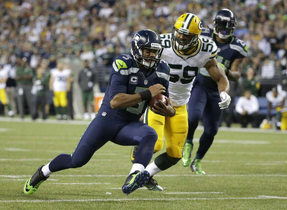 Seattle Seahawks quarterback Russell Wilson (3) scrambles as Green Bay Packers inside linebacker Brad Jones (59) pursues during the second half of an NFL football game, Thursday, Sept. 4, 2014, in Seattle. (AP Photo/Elaine Thompson) Photo: Elaine Thompson, AP