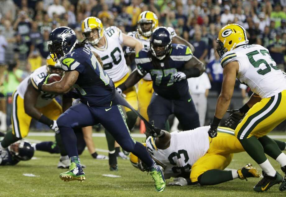 Green Bay Packers defensive end Josh Boyd (93) grabs the jersey of Seattle Seahawks running back Marshawn Lynch, left, as Lynch runs for a touchdown in the second half of an NFL football game, Thursday, Sept. 4, 2014, in Seattle. (AP Photo/Scott Eklund) Photo: Scott Eklund, AP