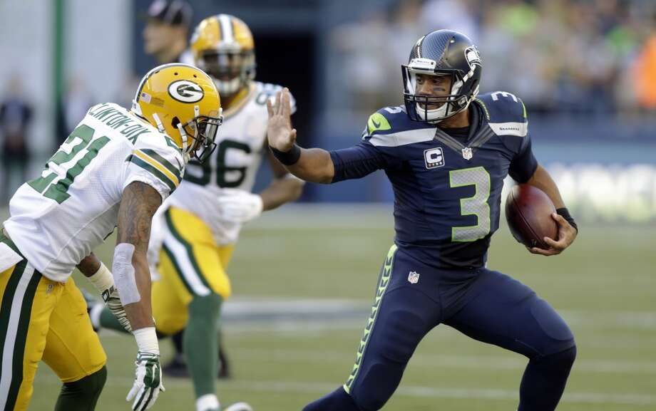 Seattle Seahawks quarterback Russell Wilson (3) avoids Green Bay Packers' Ha Ha Clinton-Dix (21) during the first half of an NFL football game, Thursday, Sept. 4, 2014, in Seattle. (AP Photo/Stephen Brashear) Photo: Stephen Brashear, AP