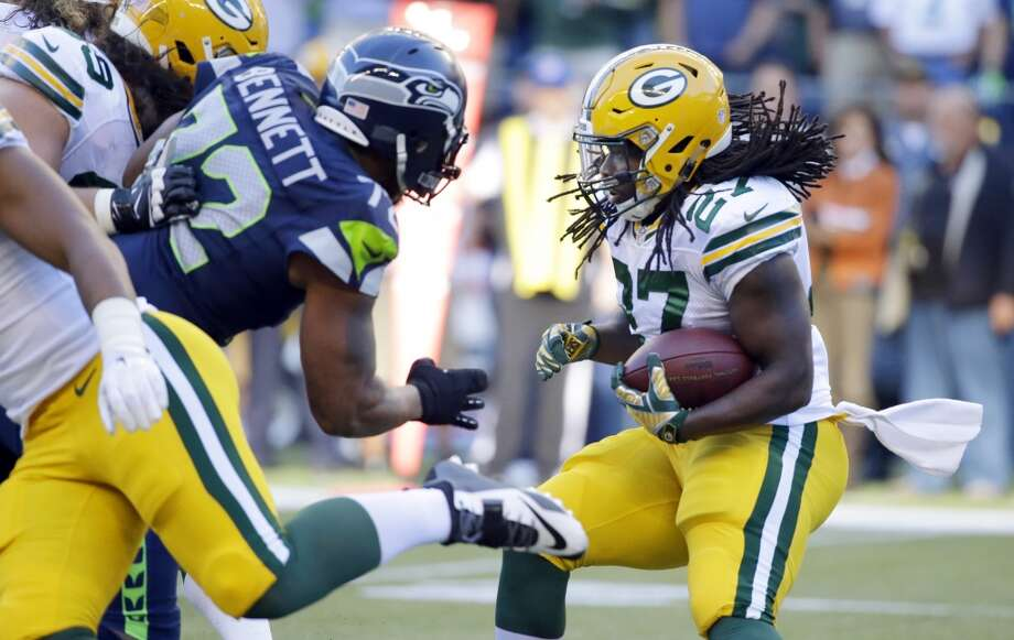Green Bay Packers running back Eddie Lacy, right, tries to avoid a tackle from Seattle Seahawks defensive end Michael Bennett, left, in the first half of an NFL football game, Thursday, Sept. 4, 2014, in Seattle. (AP Photo/Elaine Thompson) Photo: Elaine Thompson, AP