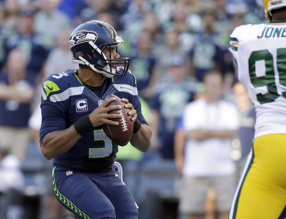 Seattle Seahawks quarterback Russell Wilson looks to pass in the first half of an NFL football game against the Green Bay Packers, Thursday, Sept. 4, 2014, in Seattle. (AP Photo/Elaine Thompson) Photo: Elaine Thompson, AP