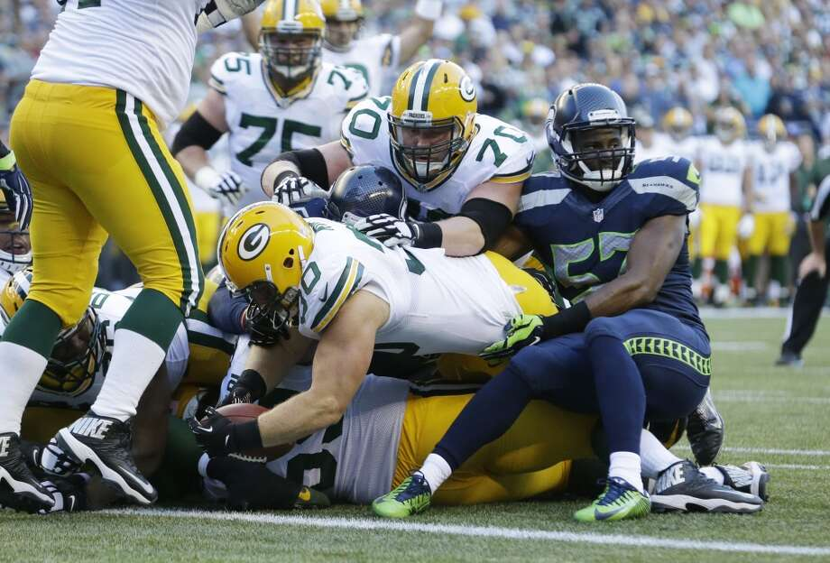 Green Bay Packers fullback John Kuhn(30) dives in for a touchdown as Seattle Seahawks outside linebacker Mike Morgan, right, tries to stop him in the first half of an NFL football game, Thursday, Sept. 4, 2014, in Seattle. (AP Photo/Elaine Thompson) Photo: Elaine Thompson, AP