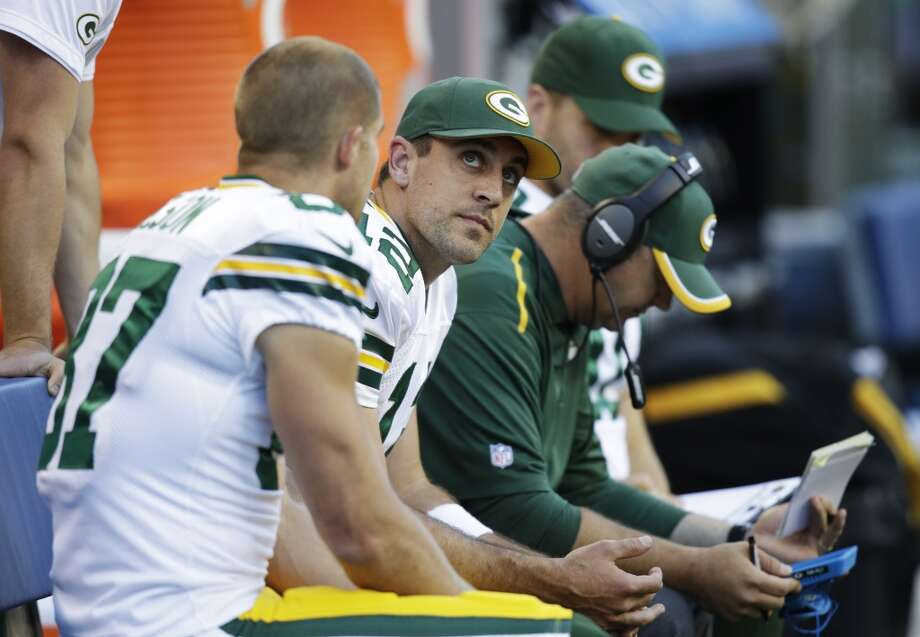 Green Bay Packers quarterback Aaron Rodgers, second from left, looks toward the scoreboard as he sits on the bench during the first half of an NFL football game against the Seattle Seahawks, Thursday, Sept. 4, 2014, in Seattle. (AP Photo/Stephen Brashear) Photo: Stephen Brashear, AP