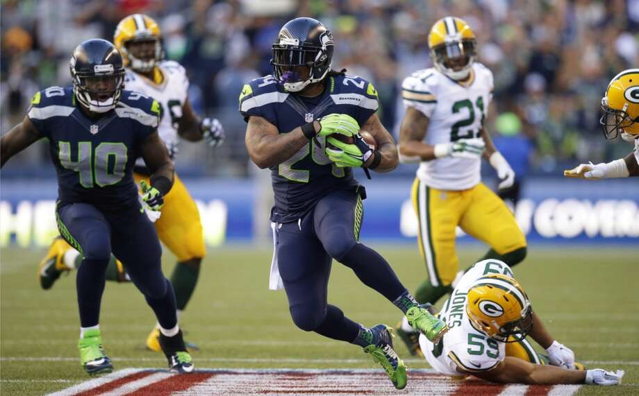 Seattle Seahawks running back Marshawn Lynch (24) runs the ball after avoiding a tackle from Green Bay Packers inside linebacker Brad Jones, lower right, in the first half of an NFL football game, Thursday, Sept. 4, 2014, in Seattle. (AP Photo/Scott Eklund) Photo: AP