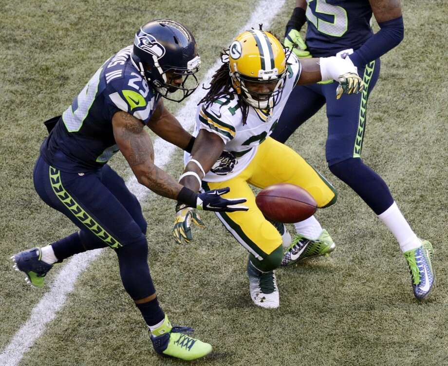 Seattle Seahawks' Earl Thomas, left, muffs the catch on a punt as Green Bay Packers' Davon House reaches for the ball in the first half of an NFL football game, Thursday, Sept. 4, 2014, in Seattle. The Seahawks got possession. (AP Photo/Scott Eklund) Photo: AP
