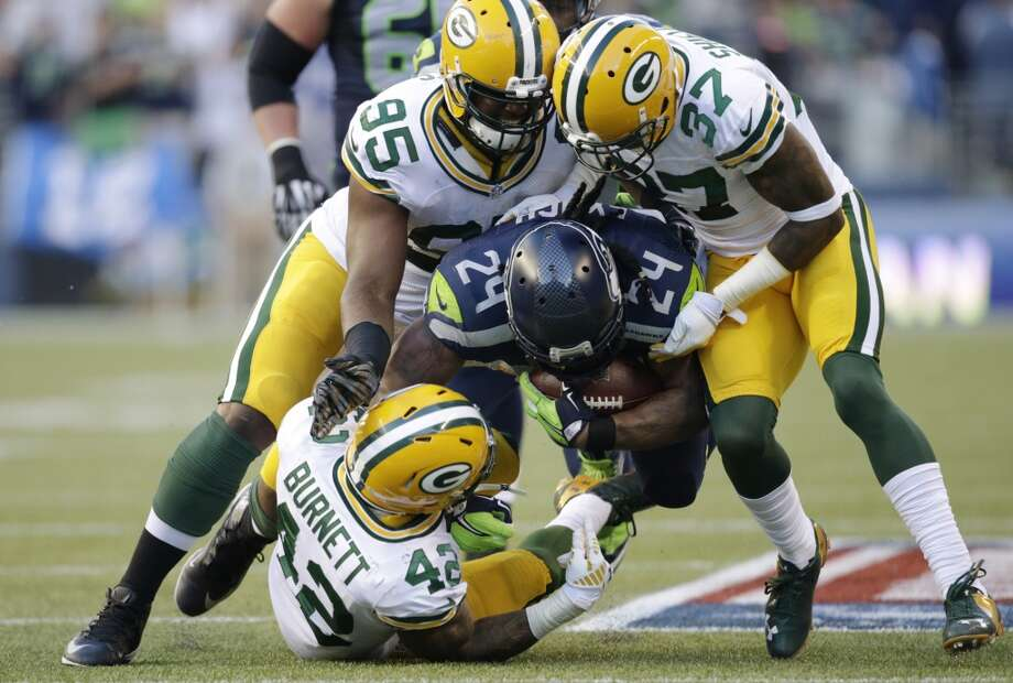 Seattle Seahawks running back Marshawn Lynch (24) is tackled by Green Bay Packers' Datone Jones (95), Sam Shields (37), and Morgan Burnett (42) as he rushes in the first half of an NFL football game, Thursday, Sept. 4, 2014, in Seattle. (AP Photo/Scott Eklund) Photo: AP