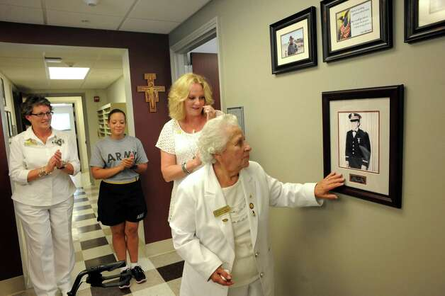 Marie Ladouceur, center, of Rensselaer, one of two remaining Gold Star Mothers from Vietnam in the Albany area, during an unveiling of a picture of her son, the late Army First Lt. Lanny G. Ladouceur , at ROTC program office of Siena College on Thursday Sept. 4, 2014 in Albany, N.Y.  Her son, Lanny, served as an Army helicopter pilot. He was 23 when he died in Vietnam on May 19, 1970. (Michael P. Farrell/Times Union) Photo: Michael P. Farrell / 00028435A