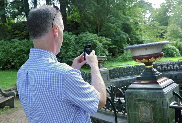 Leo Quinn of Ballston Spa takes a photo of a flower pot after hiding a $20 bill in it at Congress Park on Thursday, Sept. 4, 2014 in Saratoga Springs, N.Y. Quinn hides $20 bills somewhere in the Capital District and then post a  clue and photo to the Find A Twenty Facebook page.  (Lori Van Buren / Times Union) Photo: Lori Van Buren / 00028476A