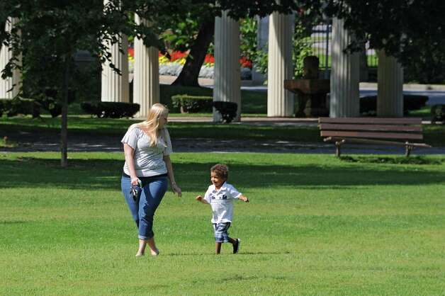 Sarah Dirzuweit of Saratoga Springs walks swiftly across the grass with Marcus, 3, a child she was babysitting, to find a $20 bill that Leo Quinn of Ballston Spa hid somewhere in Congress Park on Thursday, Sept. 4, 2014 in Saratoga Springs, N.Y. Quinn hides $20 bills somewhere in the Capital District and then post a clue and photo to the Find A Twenty Facebook page. (Lori Van Buren / Times Union) Photo: Lori Van Buren / 00028476A