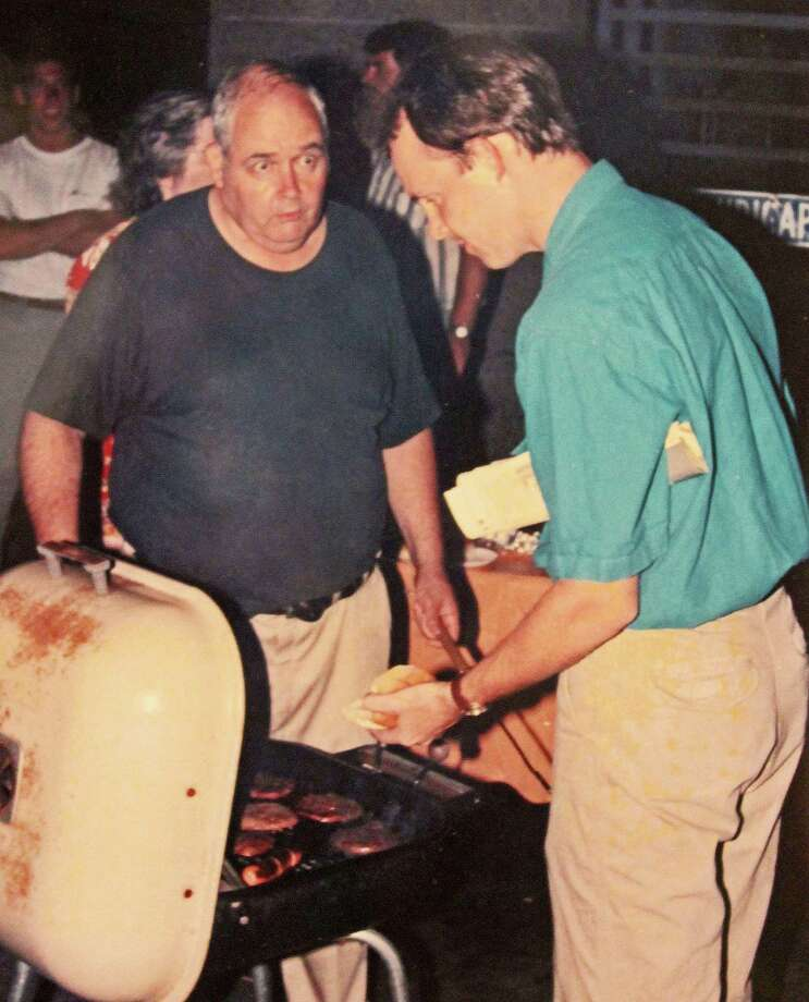 """Tom """"Sarge"""" Maloney, left, serves a burger to John Breunig during one of his summer barbecues in The Advocate parking lot in Stamford, Conn., circa 1994. Maloney, who died Aug. 26, 2014 at age 75, hosted the annual barbecues at about 2 a.m. while he was on vacation. Photo: Staff Photo / Stamford Advocate  contributed"""
