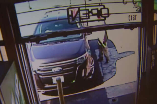 A surveillance photo taken during a car theft and kidnapping outside a West Seattle store.