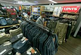 """In this Tuesday, Aug. 19, 2014 photo, shoppers browse the Levi's men's jeans department at a J.C. Penney store, in New York. Sales of jeans in the U.S. fell 6 percent to $16 billion during the year that ended in June, according to research firm NPD Group, while sales of yoga pants and other """"active wear"""" climbed 7 percent to $33.6 billion."""