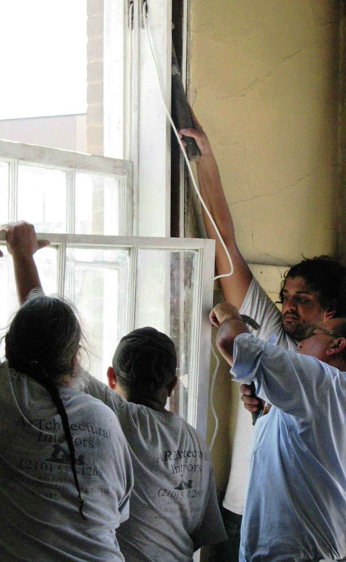 Participants in a city-sponsored historic window repair workshop replace a window with a cord and weight.
