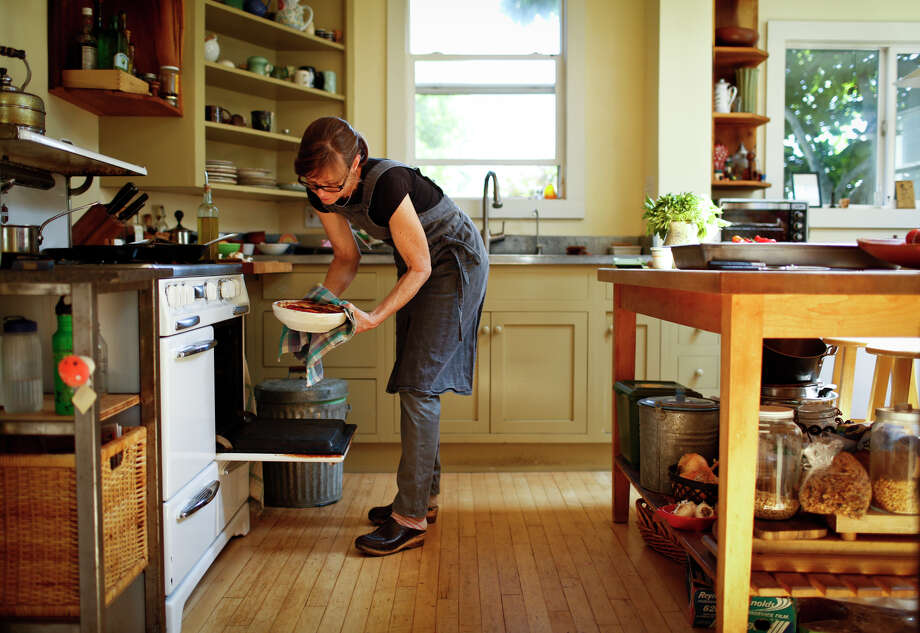 Chef-owner Kelsie Kerr prepares a Standard Fare favorite, a vegetable tian, in her Oakland home. She makes hers with a base of sauteed onions and herbs topped with thinly sliced vegetables propped up in vertical rows. Photo: Russell Yip, Staff / The Chronicle / ONLINE_YES