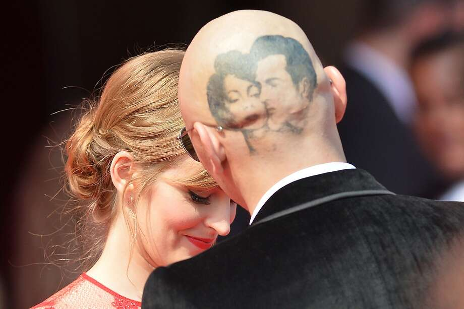 "His head doubles as a movie screen:Director James Franco unveils his head tattoo of Elizabeth Taylor and Montgomery Clift as he and Ahna O'Reilly arrive for the screening of the movie ""The Sound and the Fury"" at the Venice Film Festival. Photo: Tiziana Fabi, AFP/Getty Images"